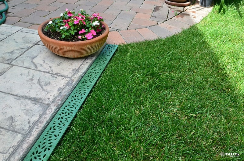 Mini Channel with NDS Botanical Polyolefin Grate Installed Next to Patio Paver